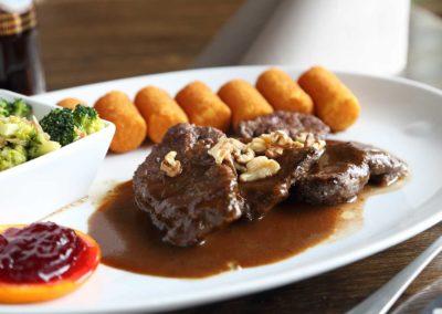 Gegrillte Hirschrückenmedaillons auf feiner Wallnusssoße mit Kartoffelkroketten und Mandelbrokkoli