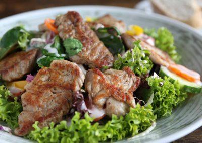 Großer Salatteller des Hauses mit Schweinefiletscheiben dazu Weißbrot