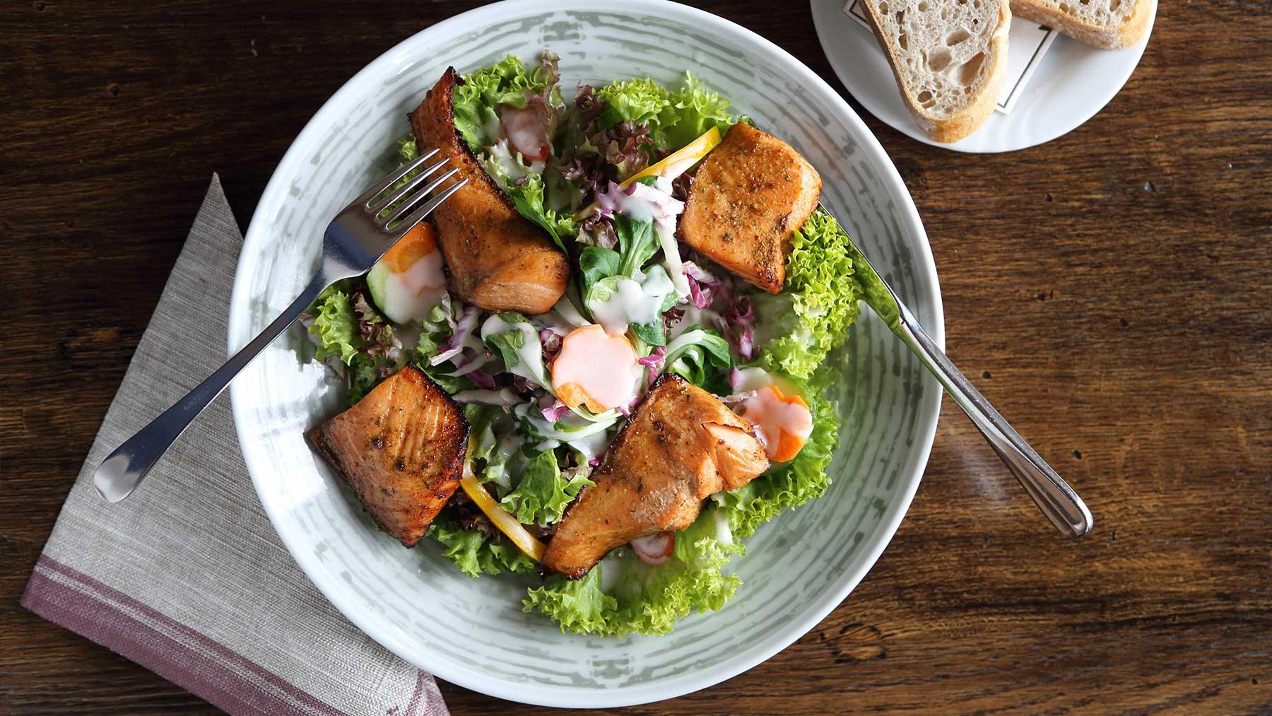 Großer Salatteller des Hauses mit gebratenem Lachs dazu Weißbrot